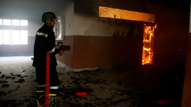 Ein Feuerwehrmann löscht ein Feuer innerhalb des verwüsteten Uni-Gebäudes.