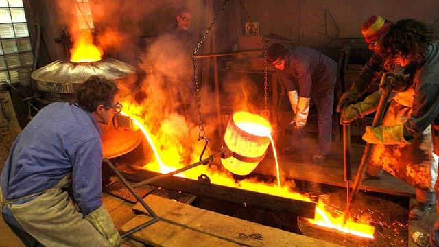 Blick in eine kleine Giesserei. Männer sind eben daran, glühendes Eisen in eine Form zu giessen.