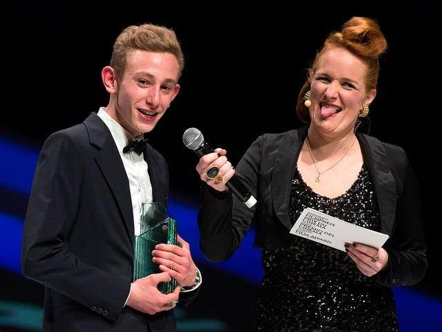 Kacey Mottet Klein steht mit Jacket und Fliege auf der Bühne erhält den «Quartz» von einer Frau, die ihm ein Microphon vors Gesicht hält und die Zunge rausstreckt.