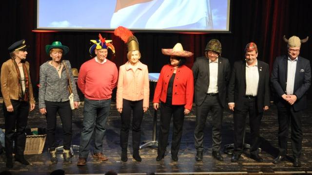 Frauen und Männer mit verschiedenen lustigen Hüten auf einer Bühne