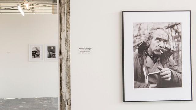 Eine Fotografie in einer Ausstellung zeigt ein Portrait eines älteren Mannes mit Zigarette.