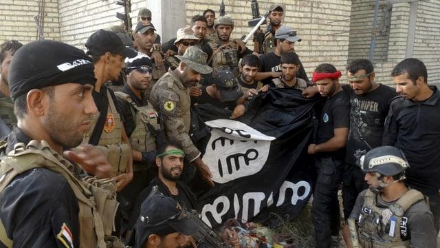Irakische Sicherheitskräfte posieren vor heruntergenommener Fahne in Ramadi.