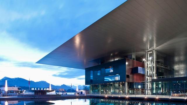 Modernes Gebäude am See mit einem grossen herausragendem Dach.