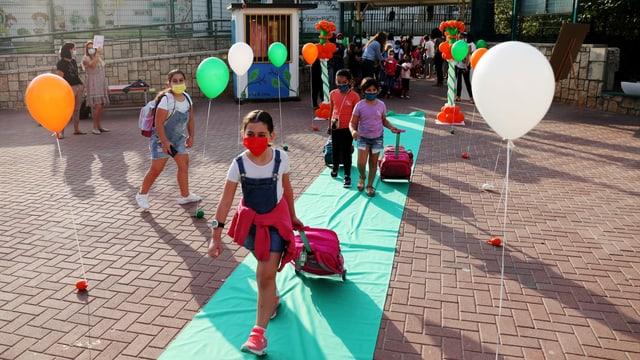 Kinder mit Maske schreiten über einen grünen Teppich. Sie haben alle Maske und einen Schulrucksack. Ballone säumen den Teppich.