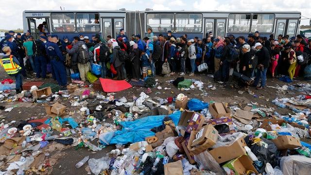 Menschen inmitten von Müll vor einem Bus