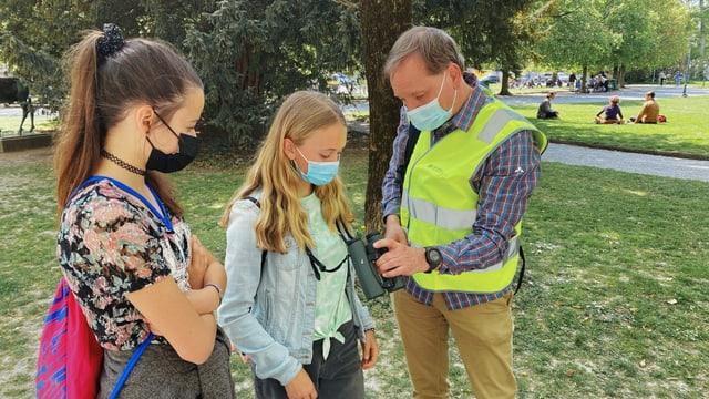 Max Ruckstuhl erklärt den beiden Mädchen die Benutzung des Feldstechers.