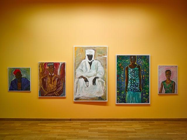 An einer gelb gestrichenen Wand hängen fünf unterschiedlich grosse Bilder. Alles Porträts von afrikanischen Frauen und Männern.