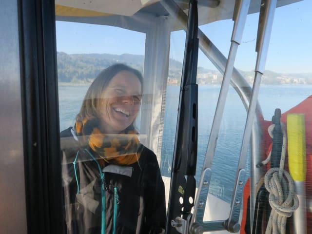 Frau steht in der Führerkabine des Motorbootes.