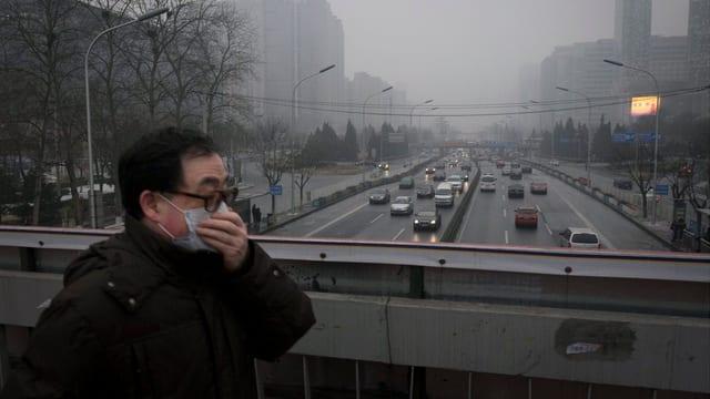 Ein Mann mit Mundschutz hastet über eine Brücke in Peking.