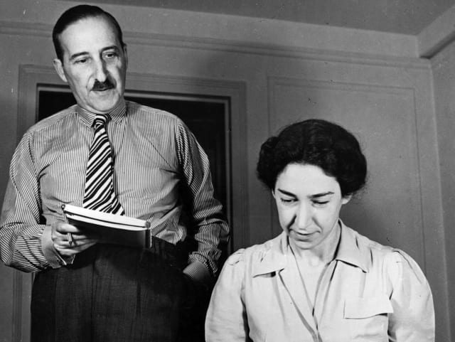 Ein Mann stehend mit einem Heft in der Hand. Eine Frau sitzend an der Schreibmaschine.