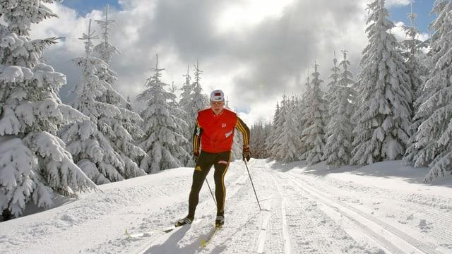 Langläufer in roten Oberteil und schwarzen Hosen in schneebedeckter Landschaft