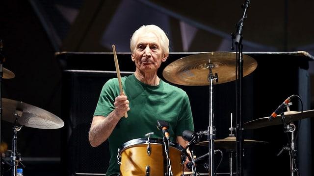 Mann mit weissem Haar am Schlagzeug.