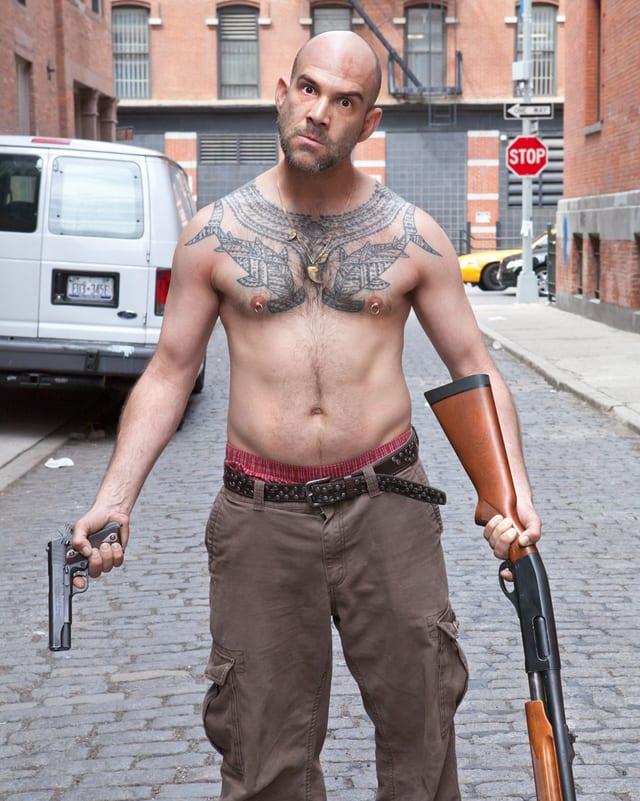 Ein Mann mit nacktem Oberkörper hält eine Pistole und ein GEwehr in den Händen, er starrt mit bösem Blick in die Kamera.