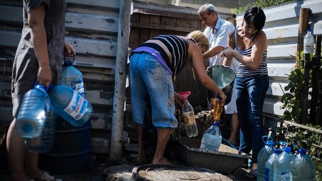Menschen füllen Wasser in Plastikkanister um. (August 2014 in Adneewka unweit von Donezk)