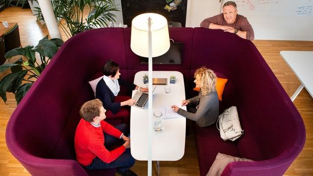 Drei Personen sitzen um einen Tisch.