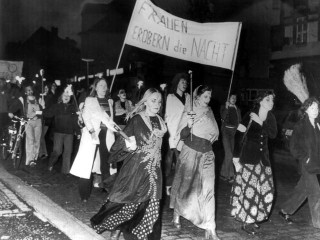 Eine Demo von Frauen in Hexenkostümen, mit Fackeln und einem Banner «Frauen erobern die Nacht».