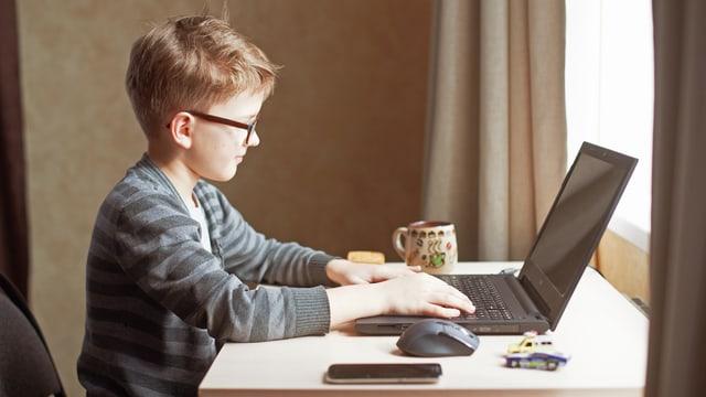 Ein Kind schreibt auf einem Computer.