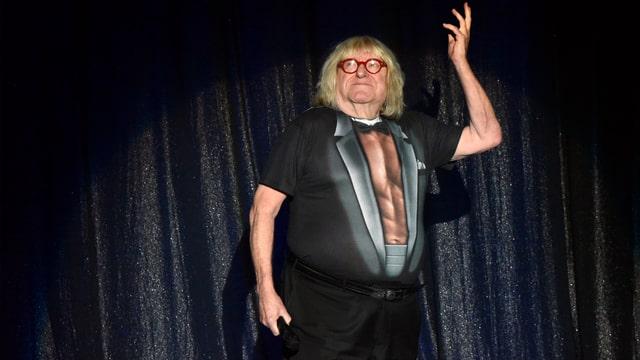 Bruce mit muskulösem Bodysuit auf einer Bühne
