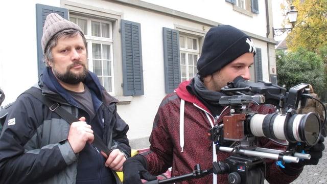 Der ukrainische Regisseur Tiazhlov mit Wollkappe und Regenjacke. Der Kameramann ist am filmen.