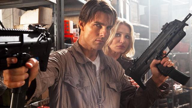 Ein Mann steht mit zwei Uzi-Maschinenpistolen vor einer Frau.