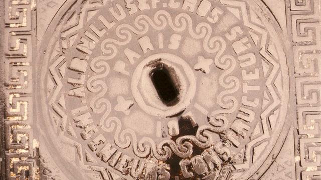 Nahaufnahme eines nassen Dolendeckels auf dem man lesen kann, dass er aus Paris stammt
