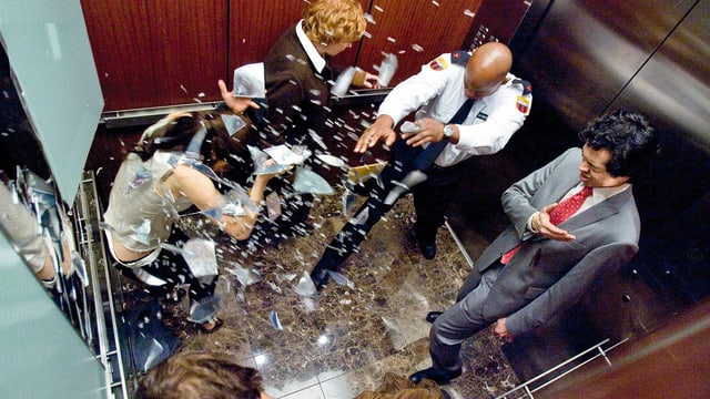 Eine Explosion in einem Lift, welche die Insassen umwirft und Scherben durch die Luft treibt.