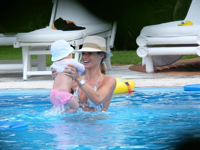 Michelle Hunziker mit Sole im Pool. Bei tragen Hüte.