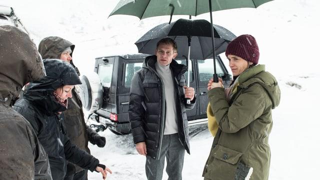 Die beiden Schauspieler stehen mit Schirmen in einer verschneiten Landschaft.