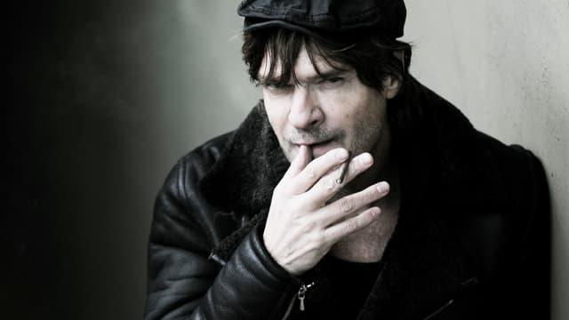 Porträt von Autor Andreas Altmann, der eine Zigarette raucht.