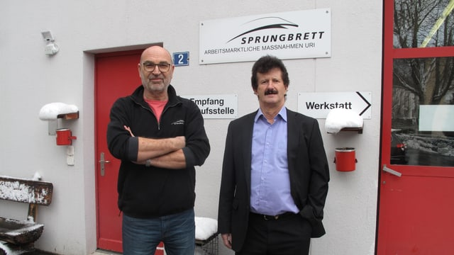 Zwei Männer stehen vor einer roten Tür.