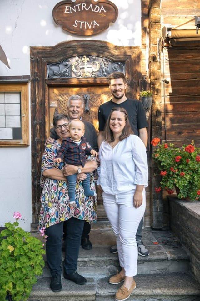 famiglia cun tat e tatta, geniturs e pop avant entrada d'ina chasa