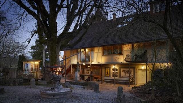 Die Mühle Hunziken bei Nacht, beleuchtet und mit einem Baum im Vordergrund.