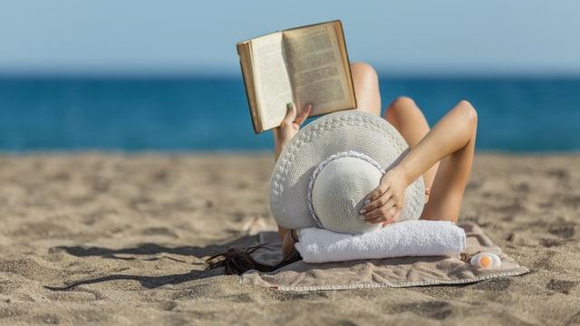 Frau mit Sonnenhut liest am Strand ein Buch