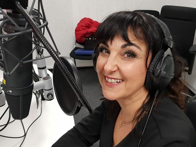 Frau sitzt im Studio hinter einem Mikrofon.