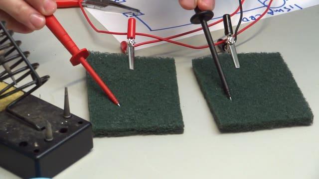 Ein Mann misst mit einem Multimeter die Ampere-Zahl eines tDCS-Geräts.