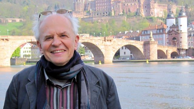 Der Autor Ralph Dutli im Porträt vor einer Brücke.