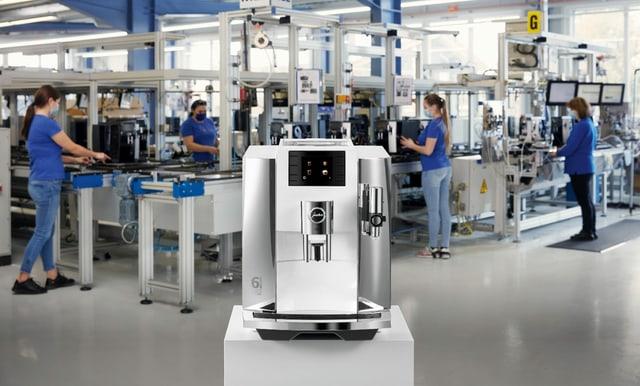 Kaffeemaschine steht in Fabrikhalle, dahinter Produktionsmaschine.