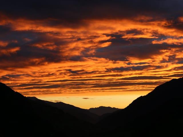 Ktischig organger Himmel über einem Tal.