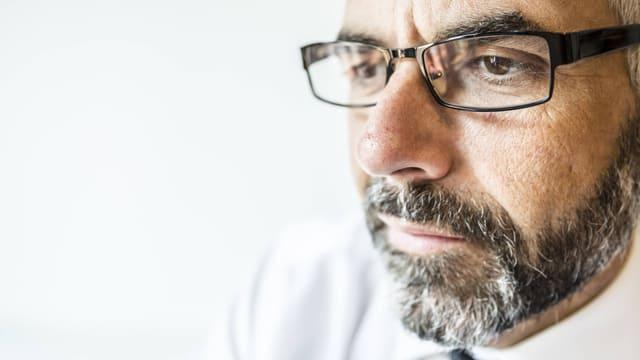 Älterer Mann mit Brille und Bart schaut konzentriert vor sich hin.
