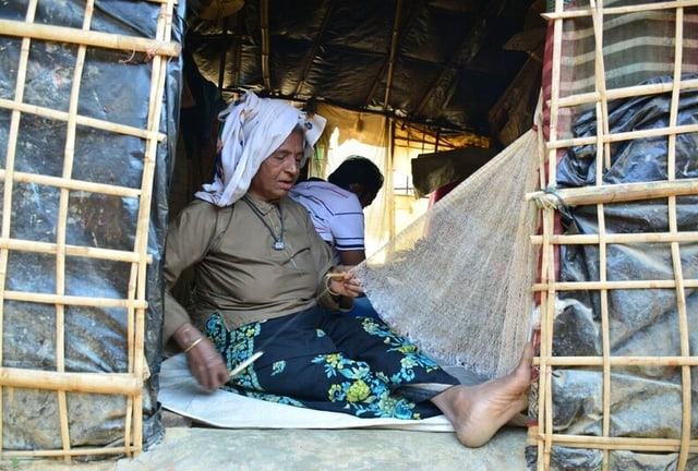 Ältere Frau sitzt in einfacher Behausung