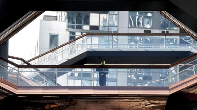 Ein Mann steht auf einer bronzefarbenen Treppe.