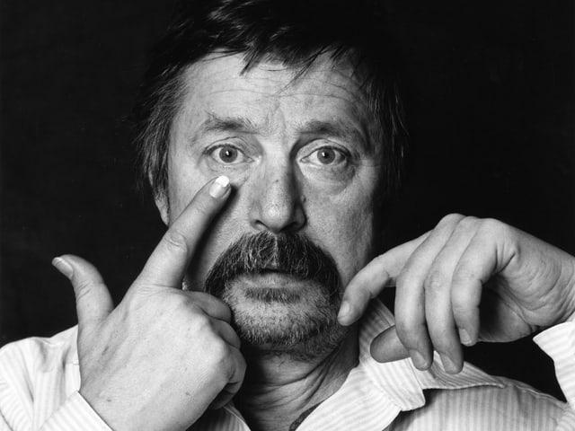 Schwarz-weiss Porträt von Wolf Biermann, der sich seinen Zeigfinger ans Auge hält.