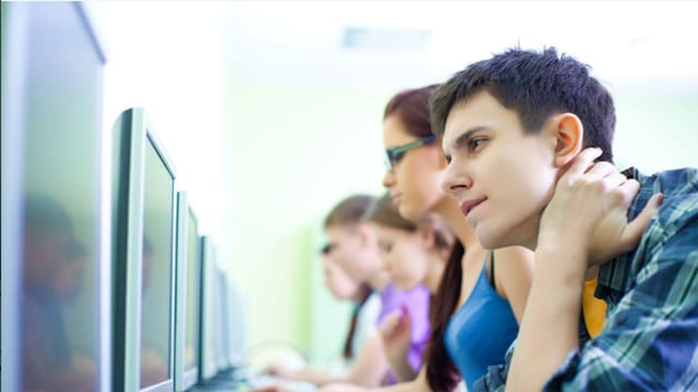 Junge Leute sitzen am Computer