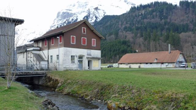 Ein Haus auf eine grünen Wiese neben einem Bach. Im Hintergrund ein grosser Stall.