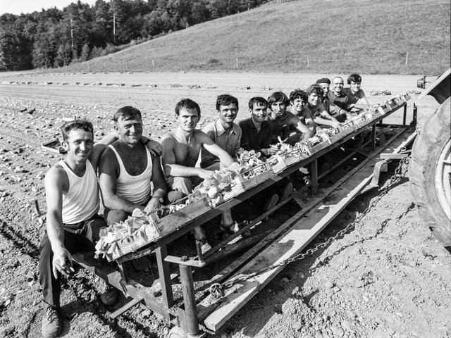 Aufgereiht hinter einem Traktor sitzen elf Männer in Unterhemden oder mit nacktem Oberkörper, sie blicken lachend in die Kamera.
