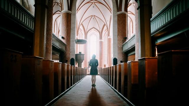 Eine Frau steht in einer Kirche