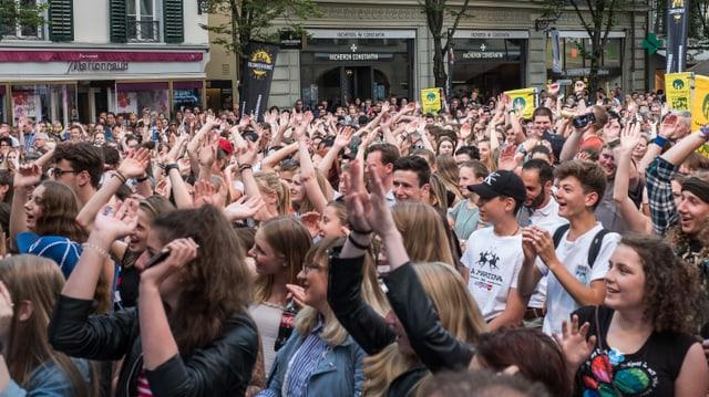 Leute stehen dichtgedrängt vor einer Bühne und jubeln