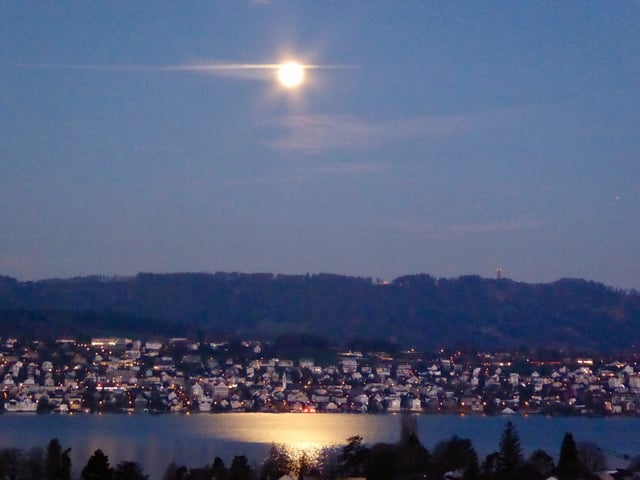 Vollmond über dem nächtlichen Zürichsee.