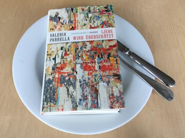Der Erzählband «Liebe wird überschätzt» liegt auf einem weissen Teller. Messer und Gabel rechts in die Seiten gesteckt.