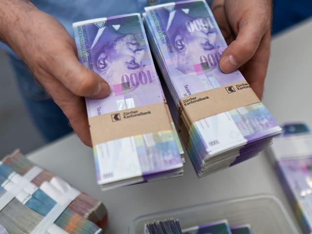 Tausender Noten in den Händen eines Bankangestellten
